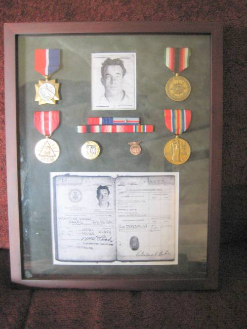 Shadowbox display of Valentine Vincent Baker's medals and images from his Merchant Marine Continuous Service Discharge Book , (Keith Olson photo)